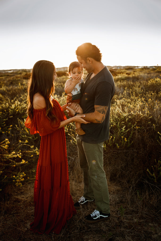 San Diego Family Photography, couple standing in a field with their young child in daddy's arms