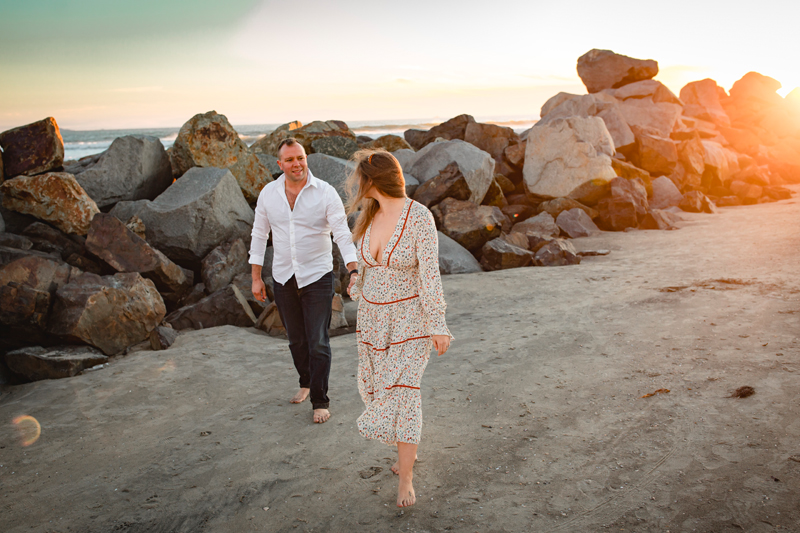 San Diego Family Photography, couple walking on the beach next to a large row of rocks